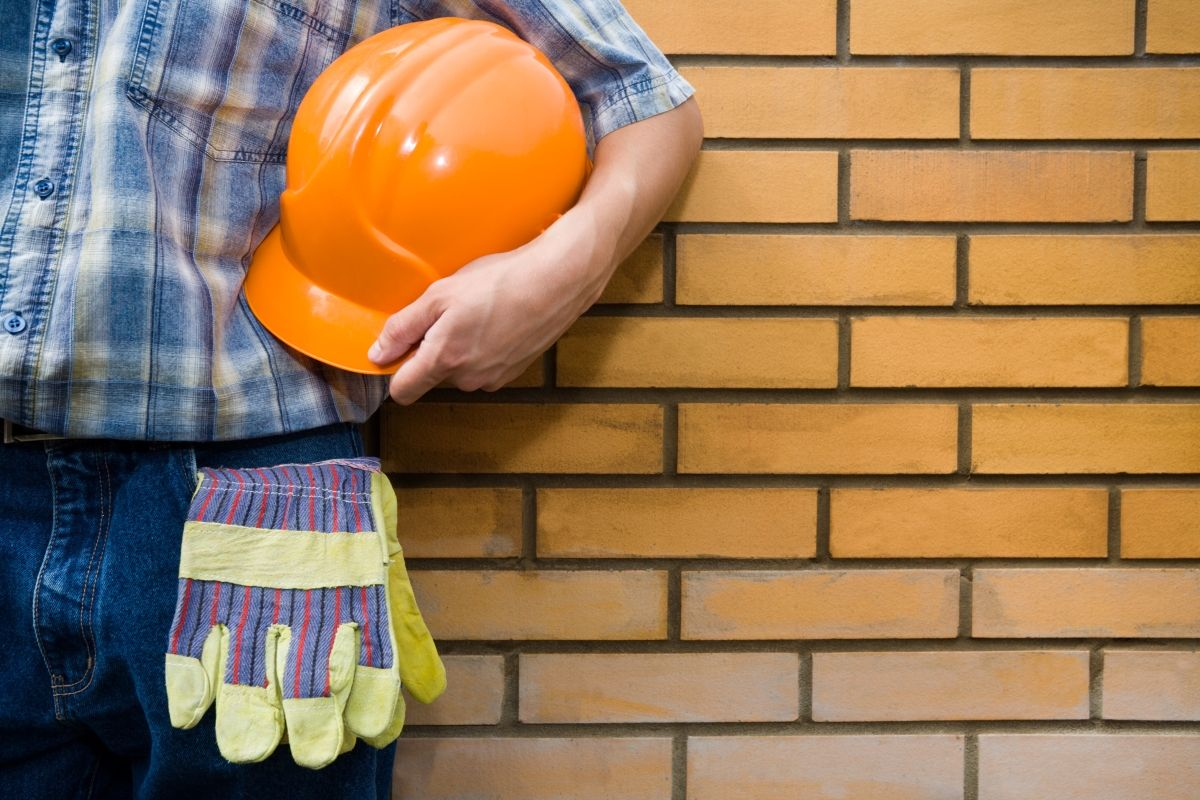 The mason holds a helmet on a background of a brick wall.
